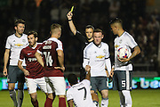Referee Stuart Attwell shows the yellow card to Northampton Town midfielder Jak McCourt (12) during the EFL Cup Third Round match between Northampton Town and Manchester United at Sixfields Stadium, Northampton, England on 21 September 2016. Photo by Phil Duncan.