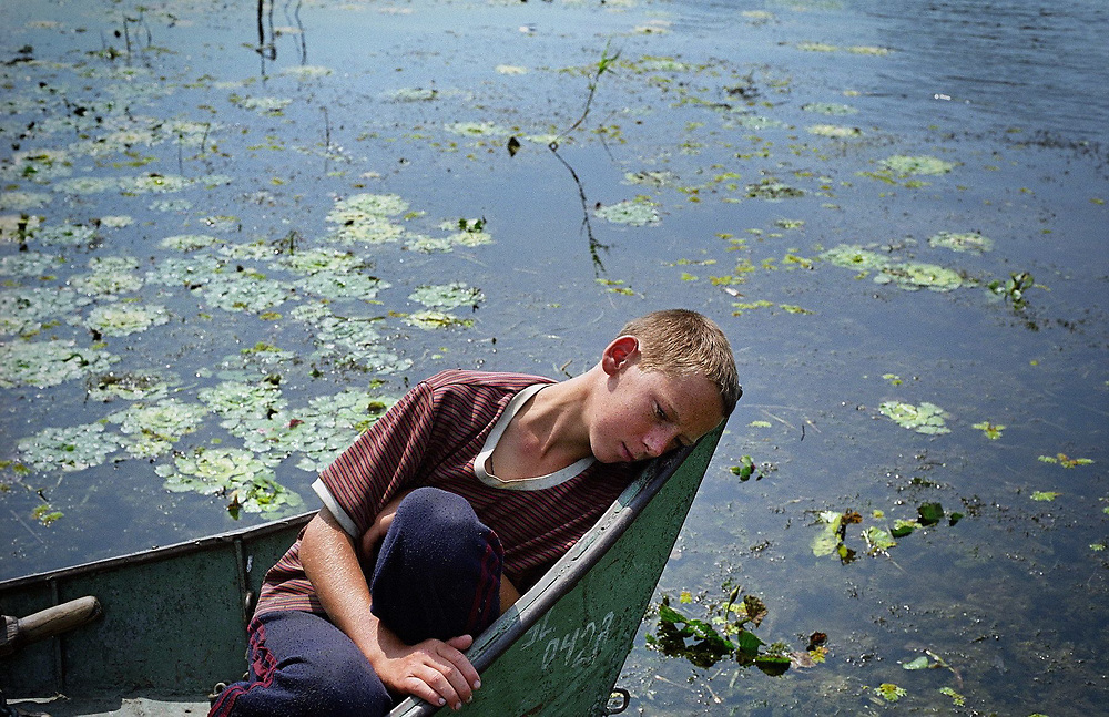 Vanea, 12 years old, sitting in a fishing boat, gave up school and joined the fishermen in Sfistofca, one of the most remote village of Danube Delta, Black Sea, Romania