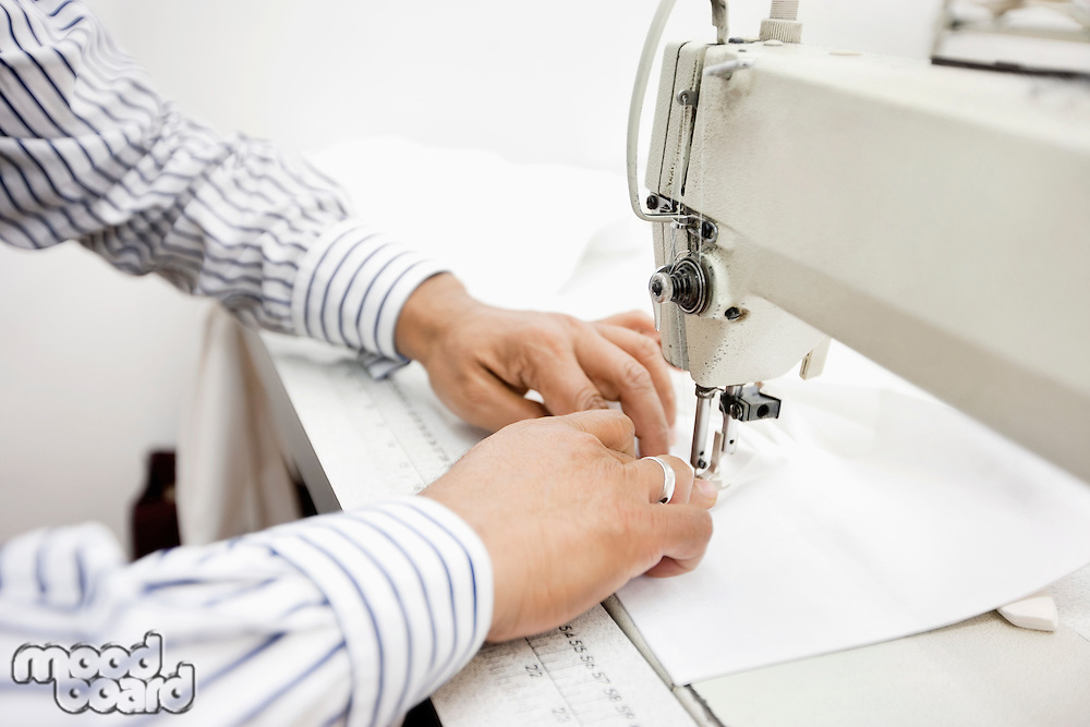 cropped image of tailor sewing cloth on sewing machine