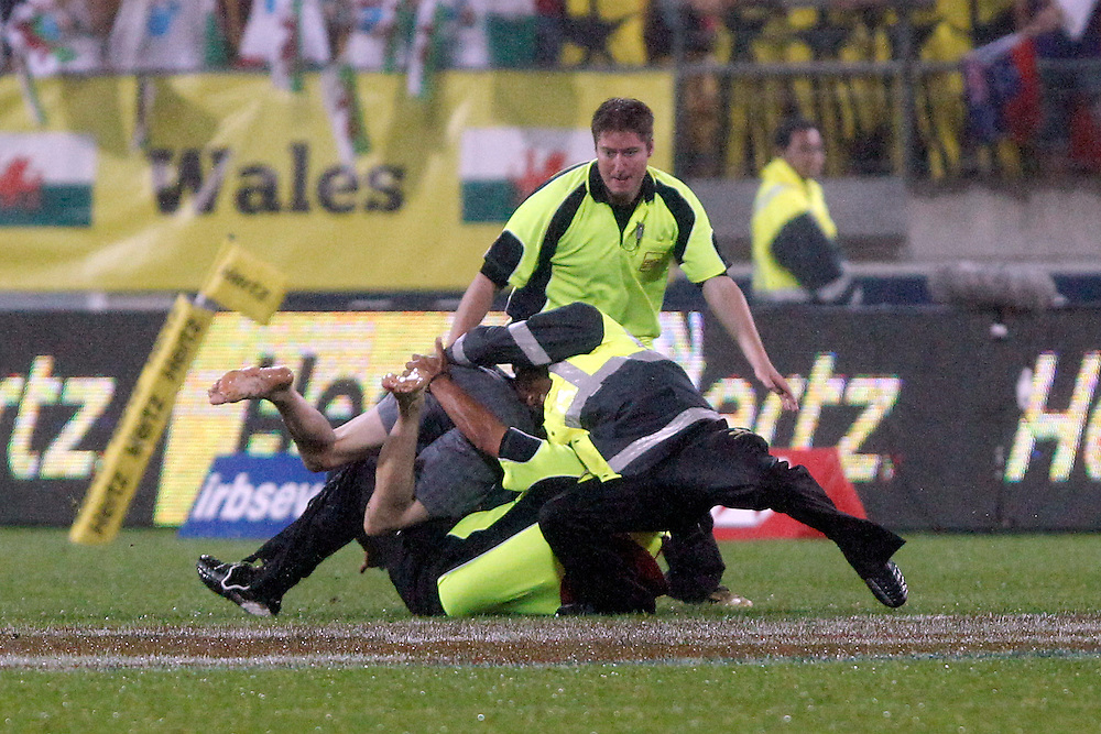 Security guards deal to a pitch invader during day two of  the IRB Sevens Tournament, Wellington, New Zealand, Saturday February 04, 2012. Credit: SNPA / Dean Pemberton