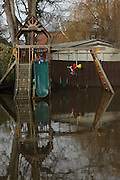 Flood waters surround children's playground on Ham Island on the river Thames near Old Windsor. Thames Valley. UK