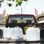 OCTOBER 25 - UTUADO, PUERTO RICO - <br /> A truck with American and Puerto Rican flags and three 5 gallon jugs from a water truck with 2,000 gallons of potable water parked near a baseball park in Utuado for resident Jose Santiago Alvarez. Troops from Fort Bragg, NC, are using a water filtration system to purify water from the nearby Lago Dos Bocas.<br /> (Photo by Angel Valentin/Freelance)