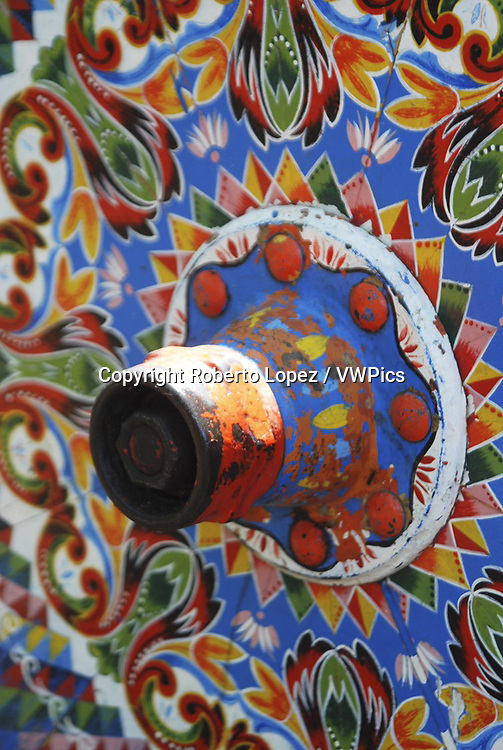 Close-up of an ox cart wheel with a traditional paint job by costarrican artisans in a cart show, Alajuela, Costa Rica