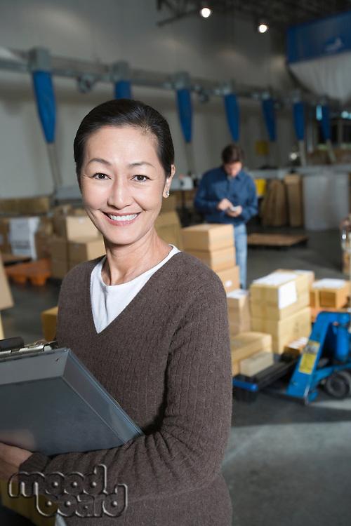 Asian woman in distribution warehouse portrait