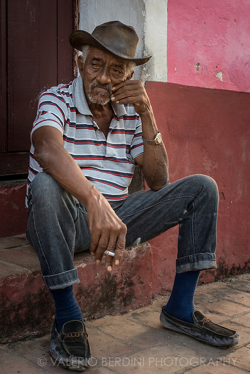 Maceo, a partially blind man, sits on a step smoking a cigarette on a side road in Trinidad, Cuba.