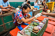 09 JUNE 2014 - YANGON, MYANMAR: A betel nut vendor sells little packets of betel in the San Pya Fish Market (also spelled Sanpya). San Pya Fish Market in Yangon is one of the largest wholesale fish markets in Yangon. The market is busiest in early in the morning, from before dawn until about 10AM.    PHOTO BY JACK KURTZ