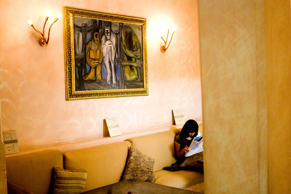 A female customer reads a magazine at the popular Hideway cafe. The interior design of this place is inspired by middle eastern style.