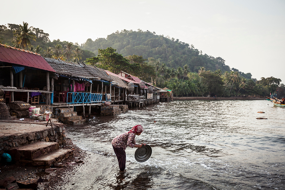 A woman washes dishes in the water off of Kep, Cambodia.