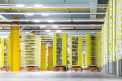 """© Licensed to London News Pictures . 04/12/2019. Manchester , UK . Robotic stock trucks move around inside a secured area within the """"MAN1"""" Amazon fulfilment centre warehouse at Manchester Airport in the North West of England . Photo credit : Joel Goodman/LNP"""