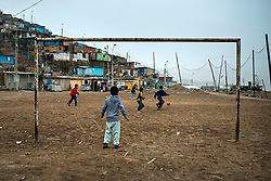 NO WEB/NO APPS - (Text available) A football field, the only recreational space for children of asientamento humano 'Nadin Heredia', where the 'Wall of shame' (Muro de la Verguenza) divides the Districts of Santiago de Surco and San Juan de Miraflores, in the city of Lima, Peru in May 2017. In Peru's capital Lima, a three-meter-high concrete wall topped with reels of razor wire separates two areas. The so-called 'Wall of Shame' - sometimes nicknamed 'Peru's Berlin Wall' - divides the urbanisation of Las Casuarinas, where some of the country's richest inhabitants live, and the poor suburb of Vista Hermosa next door. It was initially put up over fears that the inhabitants from the poor neighbourhood would steal from wealthy fellow citizens living nearby. On the rich side of the wall, the price for a square meter can exceed 2,000 dollars. To enter the area, you must show your ID to the guards watching the gate at the bottom of the hill. Former high-ranking politicians and bank directors live here. Their houses are surrounded by lush gardens and swimming pools despite the scarcity of water. Meanwhile, on the San Juan de Miraflores side, residents often fall victim to robbery and theft. They live in houses of barely 25m², made from scrap material, surrounded by the sand and earth characteristic of Lima's desert landscape. Photo by Giacomo D'Orlando/ABACAPRESS.COM