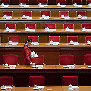 A woman places tea cups on desks for leaders in the Great Hall of the People ahead of a session of the National People's Congress. Chinese leaders are trying to improve energy efficiency to reduce both environmental damage and China's reliance on imported oil, which they see as a strategic weakness.