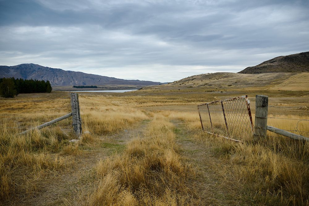 Farm gate in empty field with mountain range in background