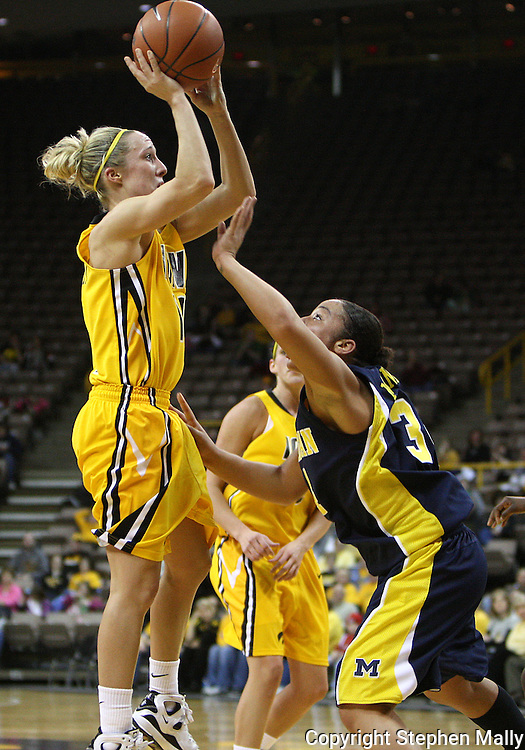 26 JANUARY 2009: Iowa guard Kristi Smith (11) puts up a shot while being defended by Michigan guard Jessica Minnfield (34) during the first half of an NCAA women's college basketball game Monday, Jan. 26, 2009, at Carver-Hawkeye Arena in Iowa City, Iowa. Iowa defeated Michigan 77-69.