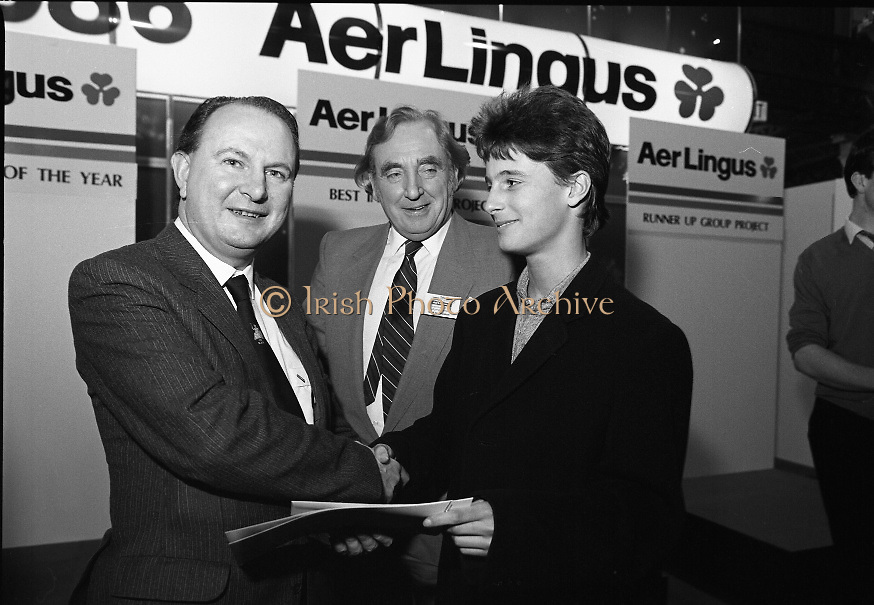 """Aer Lingus Young Scientist Exhibition..1986..10.01.1986..01.10.1986..10th January 1986..The annual Aer Lingus,sponsored,Young Scientists Exhibition was held at the RDS,Ballsbridge,Dublin.The Overall winners of the competition were Ms Breda Maguire and Ms Niamh Mulvany..They are students at The Rosary College,Raheny,Dublin. The Tanaiste, Mr Dick Spring TD was on hand to present the awards...Picture shows Mr Con Power,Director Economic Policy,Conferation Of Irish Industry presenting the CII award for Physical,Mathematical and applied Sciences to Colman Byrnes.Colman, of the Methodist College, Belfast submitted a project entitled """"The Eight Directional Joystick. Also in the picture is Mr Niall G Weldon, Chairman of the judging panel."""