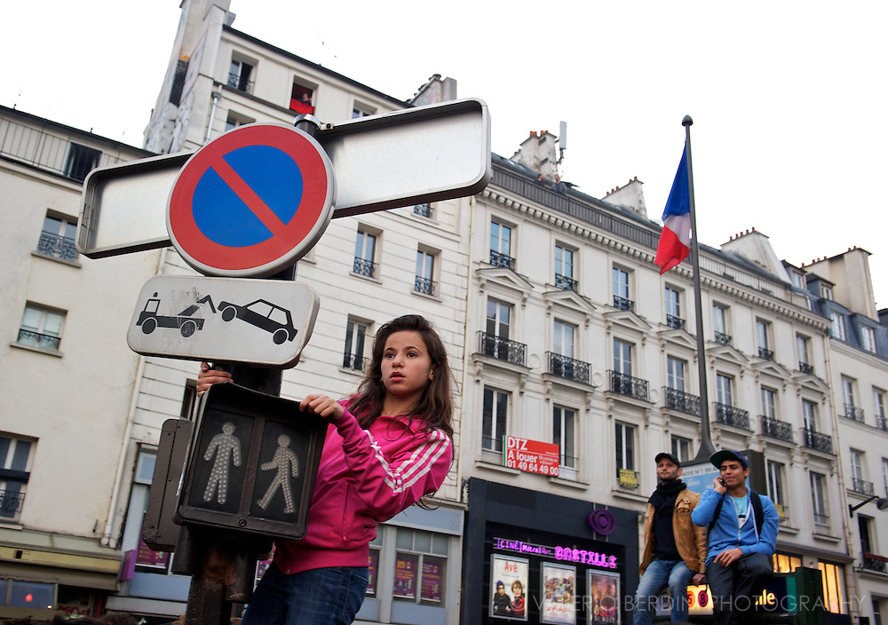 A girl climbs a traffic lights in Place de la Bastille, waiting for the new President to show up.