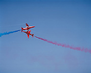The Synchro Pair of the 'Red Arrows', Britain's Royal Air Force aerobatic team cross in high-speed manoeuvre during display.