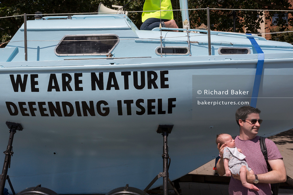 "A man stands with a young child next to a climate change boat opposite the Old Vic in Waterloo during the week-long, country-wide protest by environmental campaigners, Extinction Rebellion, on 16th July 2019, in London, England. The five-day ""summer uprising's message is for the UK government to outlaw what protesters call 'Ecocide'."