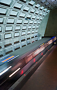 Image of a Washington, D.C. metro train speeding past Rosslyn metro station.