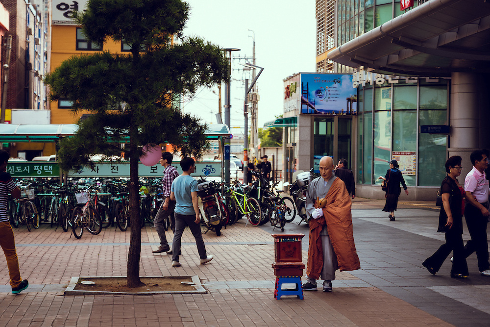 A monk halfheartedly taps his instrument and watches his donation box as passersby head into the train station and mall.<br /> Pyongtaek, South Korea