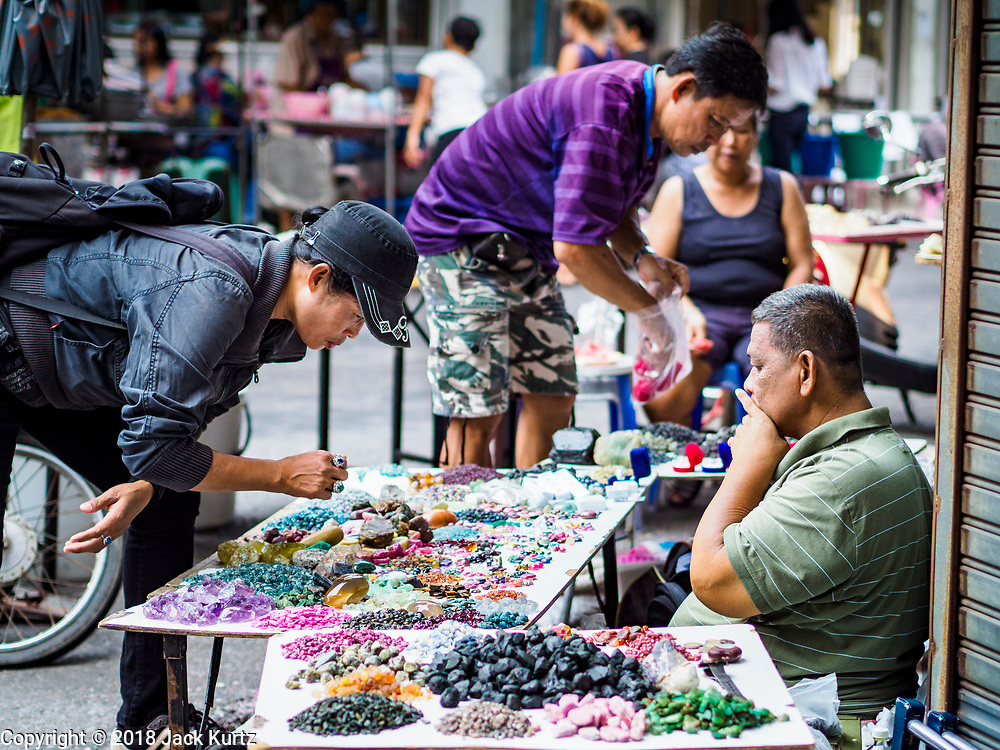 22 DECEMBER 2018 - CHANTABURI, THAILAND: A woman looks at the precious stones a Thai man in selling in the Chantaburi gem market. The gem market in Chantaburi, a provincial town in eastern Thailand, is open on weekends. Chantaburi used to be an active gem mining area in Thailand, but the mines are played out now. Now buyers and sellers come from around the world to Chantaburi for the weekend market. Many of the stones come from Myanmar, others come from mines in Afghanistan and Africa.     PHOTO BY JACK KURTZ