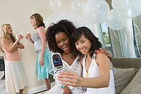 Young women photographing themselves using mobile phone at bridal shower