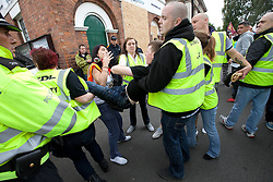 © Licensed to London News Pictures. 13/08/2011. Telford, UK. The EDL demonstrate against a paedophile ring in the small Telford town of Wellington. They eject an unwanted supporter. The group were going to march, however the Home Secretary imposed a ban on all marches in the area. About 300 EDL supporters attended. The EDL demonstration was counter-protested by about 300 people. Photo credit : Joel Goodman/LNP