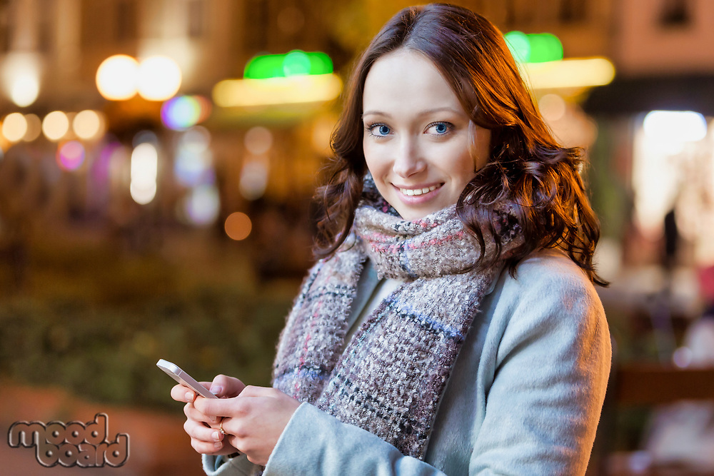 Portrait of young attractive woman smiling while using smartphone