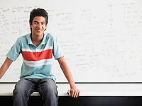 Teenage boy sitting on desktop in front of whiteboard