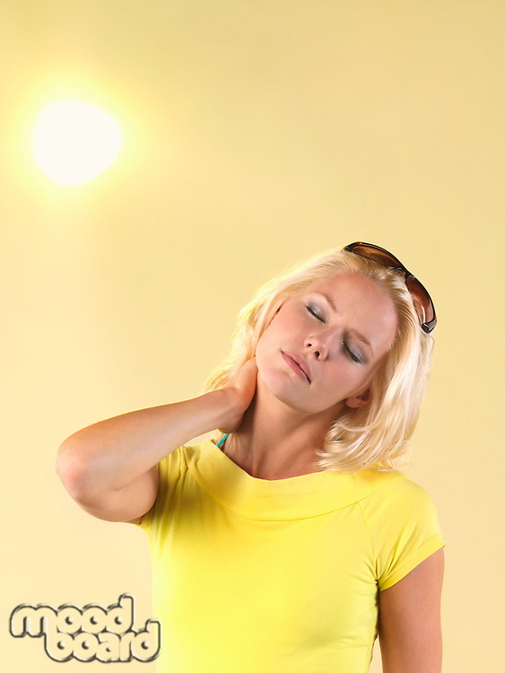 Woman rubbing back of neck on hot Summer Day
