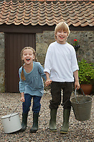 Sister and brother (5-6 7-9) holding buckets by stable portrait