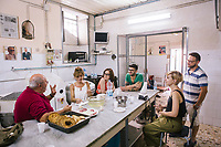 NAPLES, ITALY - 13 JULY 2017: Food writer Amedeo Colella (left) gives an explanation during a gastronomy tour at Antonio di Paola's Freselle bakery at Porta Capuana in Naples, Italy, on July 13th 2017.