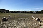 football sports field with dried up grass and pulled down goal post