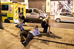 © Licensed to London News Pictures. FILE PICTURE DATED  01/01/2012. New Years Day revellers in Manchester. A man collapses on the pavement in front of a bench and an ambulance, whilst others continue their night. Please see special instructions for usage rates. Photo credit should read Joel Goodman/LNP
