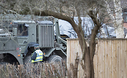 © Licensed to London News Pictures. 15/03/2018. Alderholt, UK. A vehicle (R) wrapped in a grey tarpaulin sits on a military truck waiting for removal from the village of Alderholt, south of Salisbury where former Russian spy Sergei Skripal and his daughter Yulia were poisoned with nerve agent. The couple where found unconscious on bench in Salisbury shopping centre. A policeman who went to their aid is currently recovering in hospital. Photo credit: Peter Macdiarmid/LNP