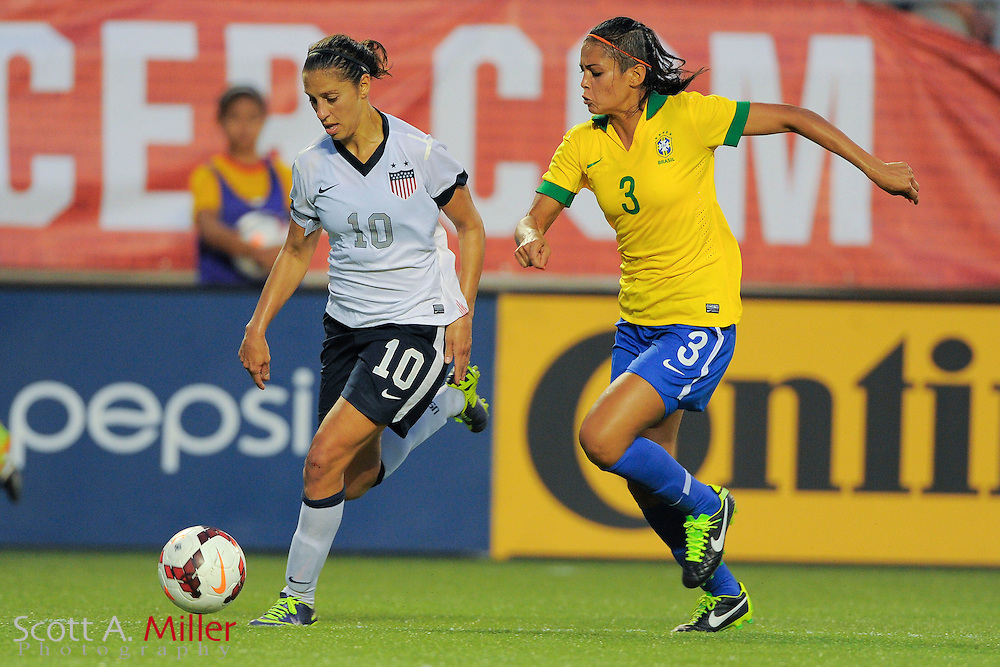 U.S. midfielder Carli Lloyd (10) brings the ball upfield as she is defended by Brazil defender Calandrini (3) during an international friendly at the Florida Citrus Bowl on November 10, 2013  in Orlando, Florida.      ©2013 Scott A. Miller