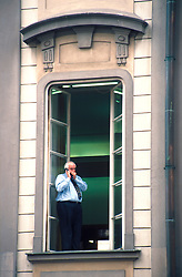 CZECH REPUBLIC BOHEMIA PRAGUE JUL96 - A clerk at the Prague Castle, residence of the President, stands in the window while talking on his mobile phone. ..jre/Photo by Jiri Rezac. . © Jiri Rezac 1995. . Tel:   +44 (0) 7050 110 417. Email: jiri@jirirezac.com. Web:   www.jirirezac.com