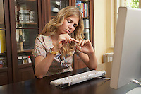 Young woman filing fingernails over computer in living room