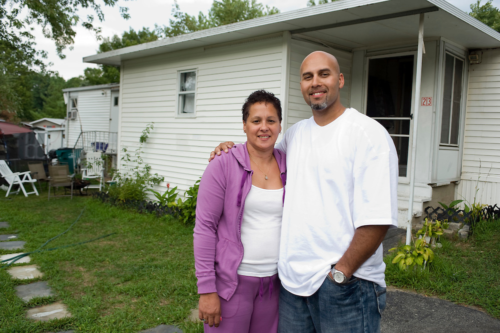 "Carlos Rosario and his aunt in front of her mobile home near Poughkeepsie, New York. Rosario lives here since he was released from prison in May 2010. ..Story: The Bard Prison Initiative.Former inmate Carlos Rosario, 35-year-old husband and father of four, was released from Woodbourne Correctional Facility after serving more than 12 years for armed robbery. Rosado is one of the students participating in the Bard Prison Initiative, a privately-funded program that offers inmates at five New York State prisons the opportunity to work toward a college degree from Bard College. The program, which is the brainchild of alumnus Max Kenner, is competitive, accepting only 15 new students at each facility every other year. .Carlos Rosario received the Bachelor of Arts degree in social studies from the prestigious College Saturday, just a few days after his release. He had been working on it for the last six years. His senior thesis was titled ""The Diet of Punishment: Prison Food and Penal Practice in the Post-Rehabilitative Era,"".Rosado is credited with developing a garden in one of the few green spaces inside the otherwise cement-heavy prison. In the two years since the garden's foundation, it has provided some of the only access the prison's 800 inmates have to fresh vegetables and fruit...Rosario now works for a recycling company in Poughkeepsie, N.Y...Photo © Stefan Falke"