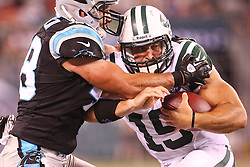 Aug 26, 2012; East Rutherford, NJ, USA; New York Jets quarterback Tim Tebow (15) is tackled by Carolina Panthers linebacker David Nixon (48) during the second half at MetLife Stadium. The Panthers defeated the Jets 17-12.