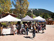 Tourists shopping at the summer Whistler Farmer's Market.  Whistler BC, Canada.