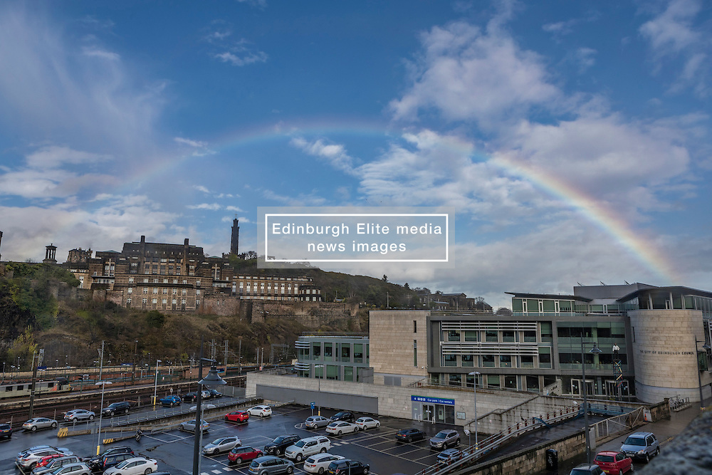 A rainbow over the city of Edinburgh. The rainbow arches over the Waverley train station and Calton Hill