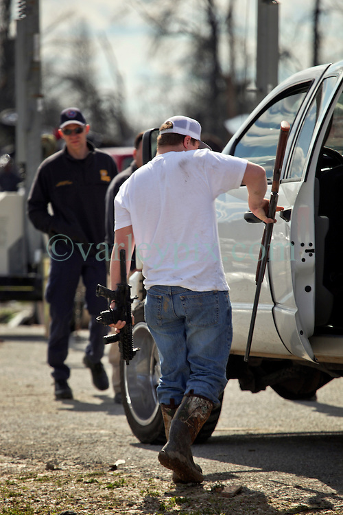 24 February 2016. Sugar Hill RV Park, Convent, Louisiana.<br /> Scenes of devastation following a deadly EF2 tornado touchdown. 2 confirmed dead. <br /> Zachary Brown recovers his weapons as he works with his family to recover all they can from their destroyed trailer.<br /> Photo©; Charlie Varley/varleypix.com