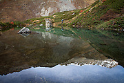 A lone hiker stands on the edge of a pristine pool reflecting a Himilayan Peak.<br /> Annapurna Trek, Nepal