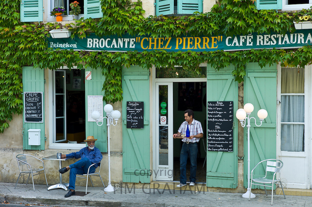 Waiter serves customer Pastis at traditional French Cafe Chez Pierre in Castelmoron d'Albret in Bordeaux region, Gironde, France