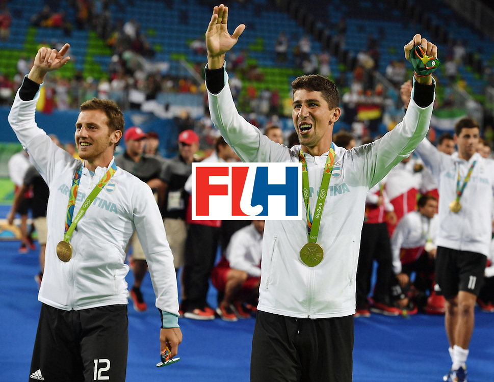 Argentina's Lucas Vila (L) and Argentina's Ignacio Ortiz celebrate with their gold medals during the men's field hockey medals ceremony of the Rio 2016 Olympics Games at the Olympic Hockey Centre in Rio de Janeiro on August 18, 2016. / AFP / Pascal GUYOT        (Photo credit should read PASCAL GUYOT/AFP/Getty Images)
