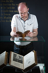 © Licensed to London News Pictures. 21/4/2016. Birmingham, UK. Rare and unseen Shakespeare items, including the first Folio are to go on display in a free exhibition at Birmingham Library from tomorrow. Pictured, Shakespeare Curator Julian Harrison with the first Folio (below), one of the main items in the exhibition. Photo credit : Dave Warren/LNP