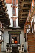 Monk running up stairs inside Jakar Dzong, Bumthang, in central Bhutan