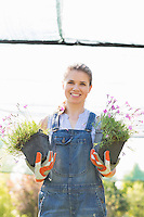 Portrait of happy female gardener holding potted plants at greenhouse