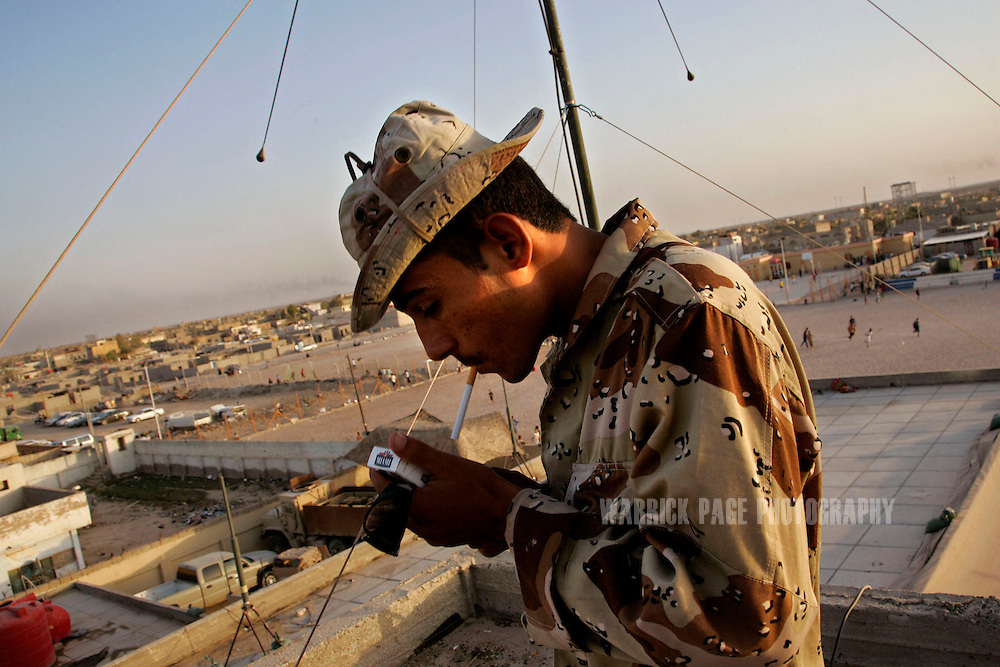 IRAQ, BASRA - JULY 4: An Iraqi Army soldier lights a cigarette while manning a lookout tower at a Military Training Team (MiTT) base in the poverty stricken neighbourhood of Hayaniyah, July 4, 2008 in Basra, Iraq. When British forces withdrew in 2007, Basra deteriorated into street battles between numerous Shiite militias and criminal gangs. In April 2008, Iraqi prime minister, Nouri al Maliki, sent two Iraqi army divisions to retake control of Basra. While the fighting has ended, unemployment is rife, at about 70 per cent. Since early 2008, Iraq's security situation has improved with oil production increasing, record government surplus and easing sectarian tensions. (Photo by Warrick Page)