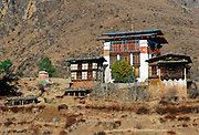 A typical Bhutanese home built in a traditional chalet style to suit the alpine surroundings.  The central building has a raised roof and wooden-shuttered windows.  The surrounding land has been terraced with stone walls.